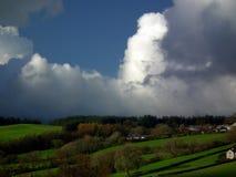 在草木茂盛的牧场的秋天云彩 免版税库存照片