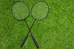 在草横渡的两副羽毛球拍说谎 免版税库存图片