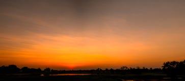 在草甸和橙色天空的美好的燃烧的日落风景在它上 惊人的夏天日出作为背景 免版税库存图片