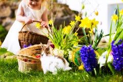 在草甸的复活节兔子有篮子和鸡蛋的 免版税库存图片