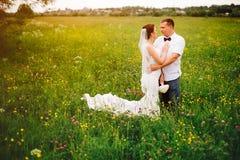 在草甸的无忧无虑的婚礼夫妇在日落期间 库存图片