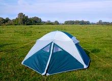 在草甸的私有野营的帐篷在河附近。 免版税库存图片