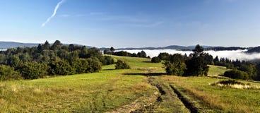 在草甸的秋天早晨有有薄雾的在上面谷和清楚的天空在Javorniky山 库存照片