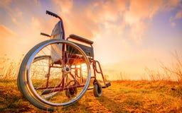 在草甸的空的轮椅日落的 免版税库存图片