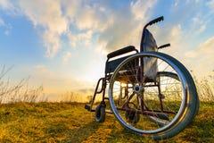 在草甸的空的轮椅 库存图片
