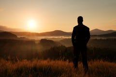在草甸的远足者立场有草和手表金黄茎的在有薄雾和有雾的早晨谷对日出 免版税库存照片