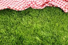 在草甸的野餐布料 免版税库存图片