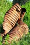 在草的一个生锈的扭转的阴沟 免版税库存照片
