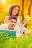 在草的一对年轻夫妇在公园在晚上 免版税库存图片