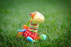 在草的一头玩具长颈鹿 库存照片