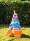 在草的五颜六色的儿童` s玩具圆锥形帐蓬帐篷 免版税库存照片