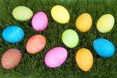 在草的五颜六色的手画装饰的复活节彩蛋 库存照片