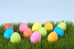 在草的五颜六色的手画装饰的复活节彩蛋 图库摄影