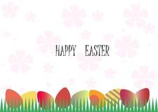 在草的五颜六色的鸡蛋在背景中变粉红色花 免版税库存照片