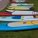 在草的五颜六色的水橇板等待使用 图库摄影
