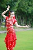 在草的亚洲中国秀丽肚皮舞表演者跳舞 免版税库存照片