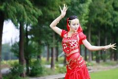 在草的亚洲中国秀丽肚皮舞表演者跳舞 免版税图库摄影