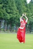 在草的亚洲中国秀丽肚皮舞表演者跳舞 库存照片