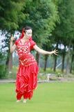 在草的优美的亚洲中国肚皮舞表演者跳舞 免版税库存照片