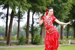 在草的优美的亚洲中国肚皮舞表演者跳舞 库存图片