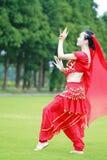 在草的优美的亚洲中国肚皮舞表演者跳舞 图库摄影