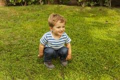 在草的全景画象逗人喜爱的兴高采烈的男婴蹲坐 库存图片