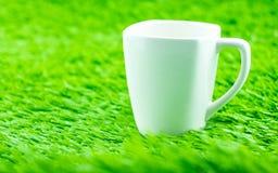 在草的加奶咖啡杯子 库存图片