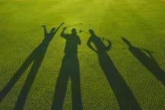 在草的四位高尔夫球运动员剪影 免版税图库摄影
