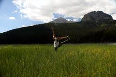 在草的女子实践的瑜伽 免版税库存图片
