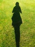 在草的妇女的阴影 库存照片