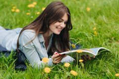 在草的妇女读书在公园 库存照片