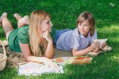 在草的家庭早餐 吃三明治的妈妈和儿子 免版税图库摄影