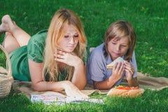 在草的家庭早餐 吃三明治的妈妈和儿子 免版税库存图片