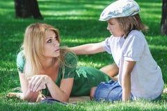 在草的家庭早餐 吃三明治的妈妈和儿子 免版税库存照片