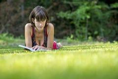 在草的少妇松弛读书 免版税库存图片