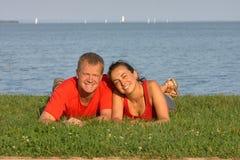 在草的年轻夫妇在海滩夏令时 库存照片