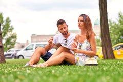 在草的年轻旅游夫妇 免版税图库摄影