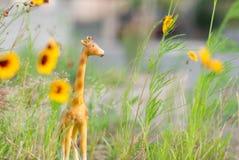 在草的微型长颈鹿小雕象和黄色花喜欢一个微型徒步旅行队 图库摄影