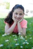 在草的愉快的青春期前的女孩 免版税库存照片