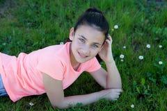 在草的愉快的青春期前的女孩 库存照片