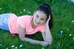 在草的愉快的青春期前的女孩 免版税图库摄影