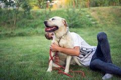 在草的拉布拉多狗与他的主要少年 免版税图库摄影