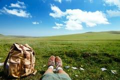 在草的旅行背包 库存图片