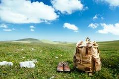 在草的旅行背包 免版税库存照片
