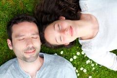 在草的有吸引力的夫妇在公园 免版税库存图片