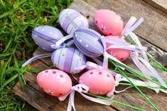 在草的桃红色和紫色塑料复活节彩蛋 库存照片