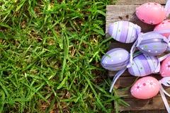 在草的桃红色和紫色塑料复活节彩蛋 库存图片