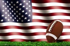 在草的橄榄球与美国国旗 免版税库存图片