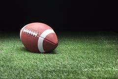 在草的橄榄球反对黑暗的背景 库存图片