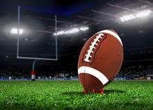 在草的橄榄球球在体育场内 库存图片
